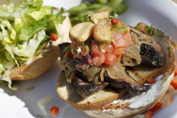The Portobello and Sausage Burger is made with grilled portobellos, homemade Native Sausage Seitan, caramelized onions, salsa pomodoro, sweet roasted garlic, creamy pumpkin seed pesto and mayo.