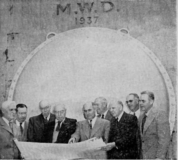 Officials of the Metropolitan Water District and the Foothill Municipal Water District in January 1953 stand at the point on the Metropolitan aqueduct line near the Rose Bowl, studying a map.