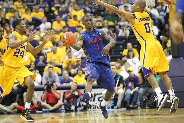 Florida Gators guard Kenny Boynton (1) passes the ball away from LSU Tigers guard Charles Carmouche (0) and guard Malik Morgan (24) during the second half at the Pete Maravich Assembly Center. Florida defeated LSU 74-52.