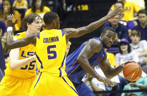 Florida Gators center Patric Young (4) is defended by LSU Tigers forward Shavon Coleman (5) and Andrew Del Piero (55) during the first half at the Pete Maravich Assembly Center. Florida defeated LSU 74-52.