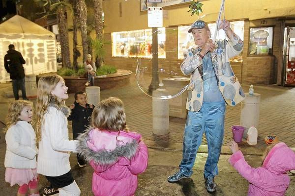 "Bill Ackroyd, known as ""The Bubble Man,"" entertains a group of children during Surf City Nights Street Fair and Farmers Market in Huntington Beach on Tuesday."