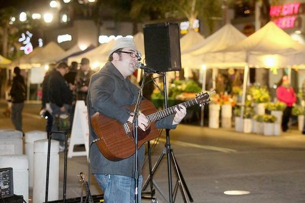Local musician Danny Maika performs during Surf City Nights Street Fair and Farmers Market in Huntington Beach on Tuesday.