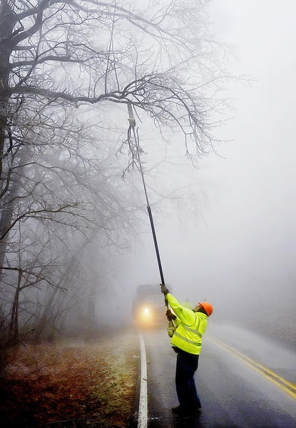 On a foggy Ritchie Road near Cascade, Washington County roads crew employee Dwayne Feigley trims ice-covered branches hanging low on Wednesday.
