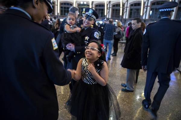 Anaya Feliciano, 9, shakes hand with instructor Rea Barnes as he father Jose Feliciano holds daughter Nevaeh, 1, following graduation ceremony for class of Chicago Police Department detectives at Navy Pier.