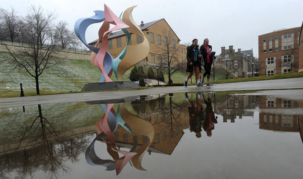 "David Cerulli's sculpture titled  ""In a State of Rejuvenescence"" along with Anne Bracaglia of Amberler (left) and Lisa Campbell of Summit, N.J., both seniors at Lehigh University reflect in a puddle in the Rauch Business Center's courtyard in Bethlehem on a rainy Wednesday morning. The sculpture was installed in 1997 and is one of many in the outdoor sculpture collection at Lehigh University in Bethlehem."