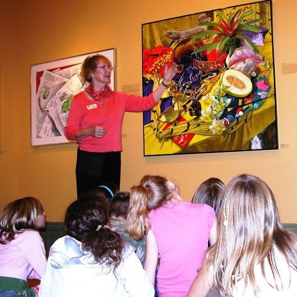 Crooked Tree Arts Center docent volunteer Judy Knowles shares insight into a large painting with a local school group.