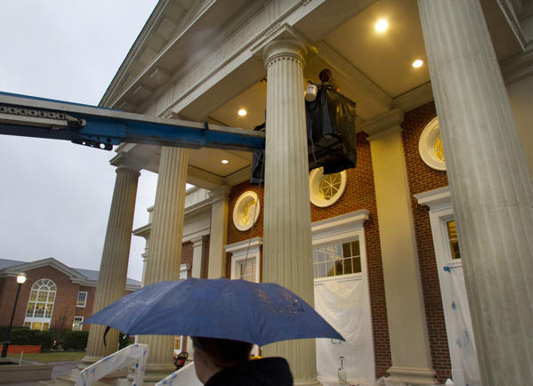 A Christopher Newport University student shields herself from the rain Thursday as workers put the final touches on the Pope Chapel early Thursday. The 14,000-square foot structure is scheduled to open this month and is located between the Trible Library and Ferguson Center for the Arts.