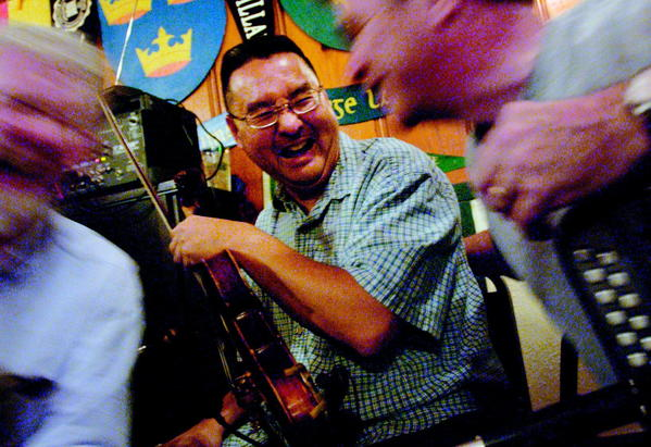 Violinist Dave Abe (center) of the Baltimore Ceili Band, shares a laugh at J. Patrick's Irish Pub back in October 2003.