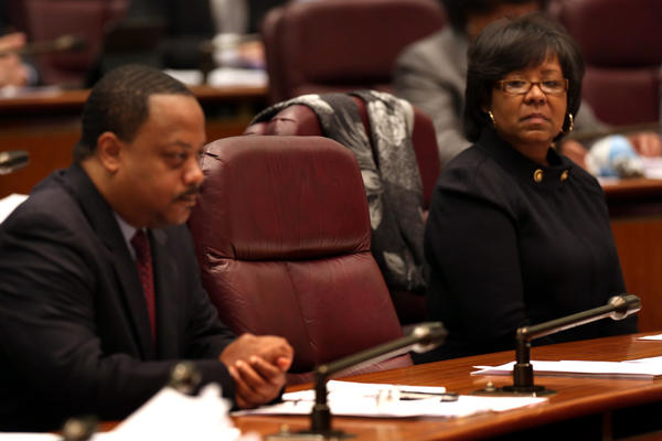 Aldermen Roderick Sawyer, 8th, and Michelle Harris, 6th, attend today's Chicago City Council meeting. The empty chair between them was that of former alderman Sandi Jackson.