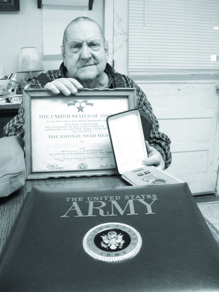 Robert H. Mitchell holds an Army certificate given to him with a Bronze Star medal he earned for bravery during World War II.