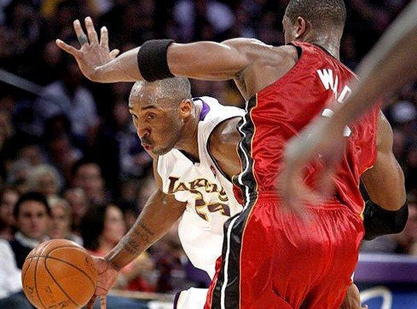 Lakers guard Kobe Bryant tries to drive his way around Heat guard Dwyane Wade.