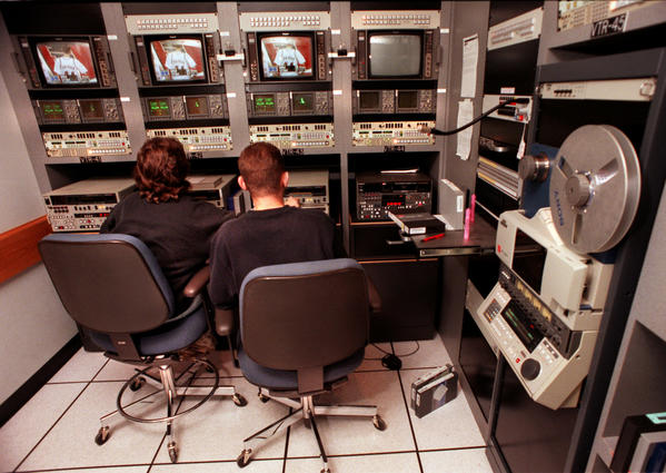 Employees edit a college basketball highlight reel in an ESPN production control room in preparation for college basketball coverage.