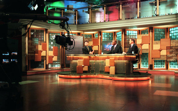 Anchor Brian Kenny, at left, and college football analysts Rod Gilmore and Mike Gottfried tape an ESPN Heisman Trophy preview show on one of four sets in ESPN's main studio.
