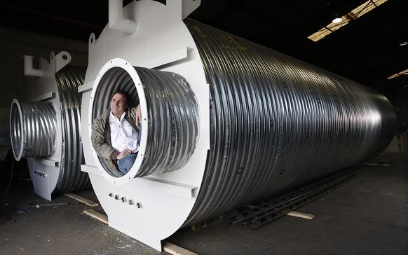 Ron Hubbard, owner of Atlas Survival Shelters, sits in the escape tunnel of a 33-foot corrugated metal underground shelter that his company assembles at his small plant in Montebello.