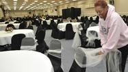 Louise Johnson popped out of her seat at the Patapsco Arena in South Baltimore — taking a break from tying decorative gold and silver sashes to the backs of hundreds of chairs — and smiled warmly at a man delivering newly pressed gleaming white tablecloths.