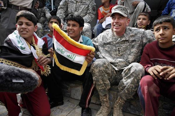Gen. David Petraeus sits with Iraqi children during a youth soccer tournament in central Baghdad on March 1, 2008.