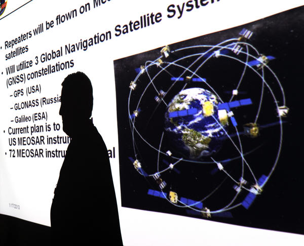 The shadow of Chris O'Connors, the NOAA/SARSAT program manager, is projected onto a screen showing a satellite system planned for the future.