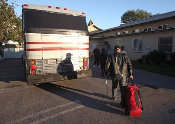 Douglas Webb, who is homeless heads for the bus that is part of a pilot program to shuttle homeless from the Lightbouse Church in Costa Mesa to the OC Armory.