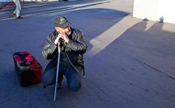 Douglas Webb, who is homeless, waits for a bus that is part of a pilot program to shuttle homeless from the Lightbouse Church in Costa Mesa to the Armory.