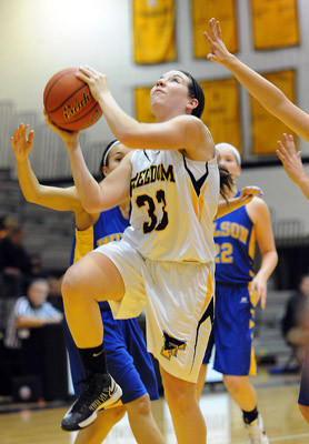 Freedom's Taylor Garza (front) drives to the basket in front of Wilson's defense during their high school girls basketball game Thursday night.