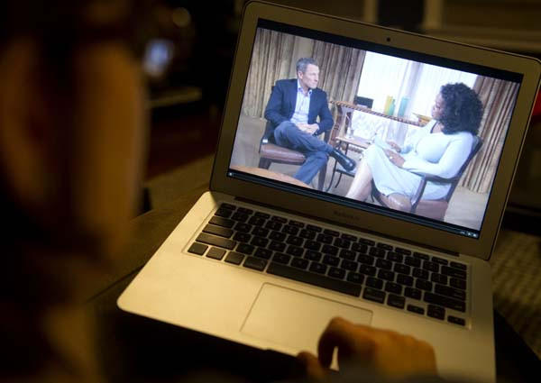 A woman watches on her computer as Oprah Winfrey questions cyclist Lance Armstrong during an interview recorded on Monday and shown on Thursday night.