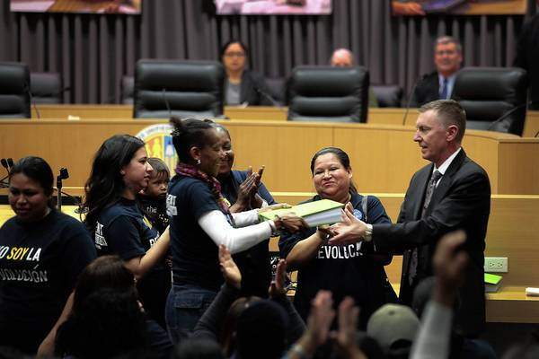 Latrice Gamble hands a binder full of parent-trigger petitions to L.A. Unified Supt. John Deasy. More than 100 parents from 24th Street Elementary were greeted cordially by Deasy.