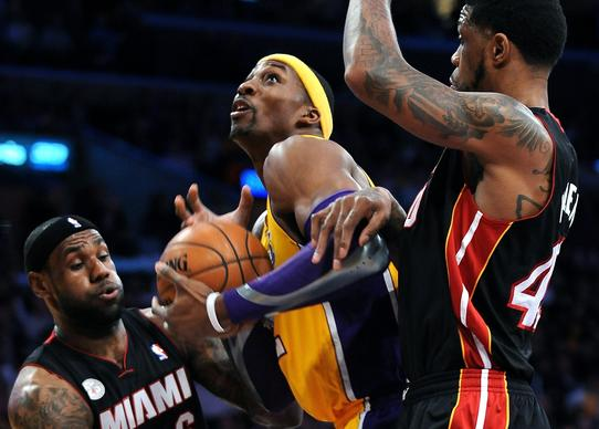 Dwight Howard attempts a shot on Heat forwards LeBron James and Udonis Haslem during the first half of their game last