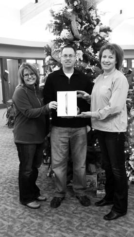 Scott Isaak of Aberdeen won an iPad on Nov. 30 during Plains Commerce Bank's e-statement campaign drawing. From left are Jodie Kanas, assistant vice president of retail banking; Isaak; and Kellie Ecker, marketing officer.