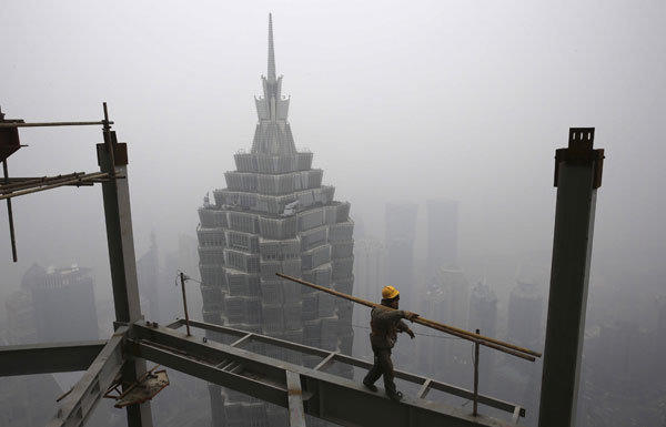 China's GDP rose 7.9% in the fourth quarter, beating expectations and softening the blow of the country's slowest annual growth in a decade. Above a worker at the construction site of the Shanghai Tower, with the city's skyline shrouded in fog.