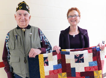 The South Dakota School for the Blind and Visually Impaired in Aberdeen recently honored another Quilts of Valor recipient during the school's Christmas program. The quilts are the school's way of saying ¿thank you¿ for their service in the armed forces, sacrifice, and valor. From left are quilt recipient Edward Scheer (U.S. Army, 1954-56) and Jayne Reuer, area director of Quilts of Valor program.