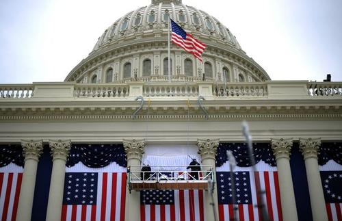 Two workers adjust the U.S. flag on the Capitol as preparations continue for President Obama's second inauguration ceremonies.