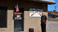 "For J. Robert Hayes, a competitive shooter and owner of The Gun Shop in El Centro, business is booming. ""Look at my case,"" he said, gesturing at a display case that was nearly empty. ""These racks are normally full,"" he said, pointing at a rack behind him that holds shotguns."
