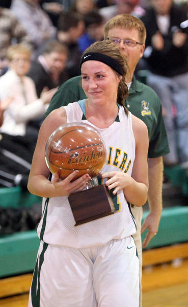 Aberdeen Roncalli's Mollee Karst was honored for setting a new school scoring record by girls basketball coach Derek Larson (behind Karst) during Thursday night's game at the Roncalli High School gym.