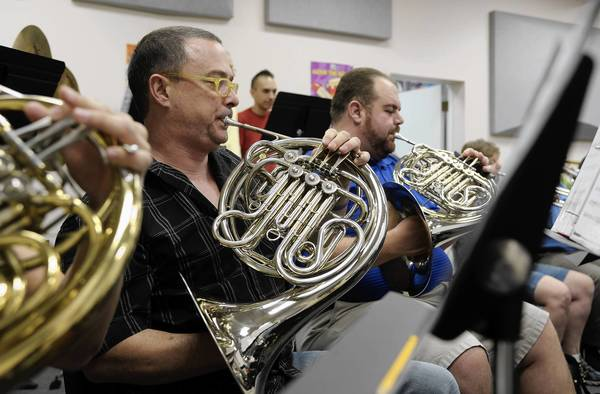 Michael Leigh and Adam DeRosa play their french horns while practicing for an upcoming concert for the South Florida Pride Wind Ensemble.