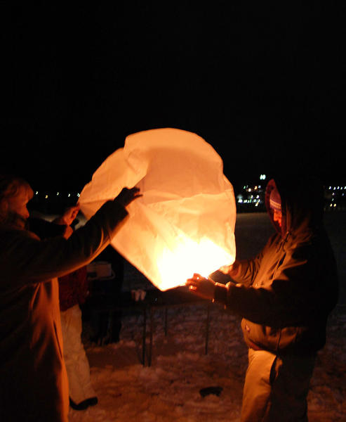 Lynette Hahn, aunt of Maria Tuck, and Maria's oldest brother, Addison tuck, release a lantern in memory of Maria on Thursday at the Petoskey waterfront.