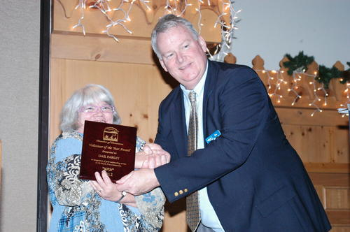 "Boyne City Chamber of Commerce director Jim Baumann presents Gail Farley with the chamber's Volunteer of the Year Award Thursday. Farley is the main driving force behind the Northern Michigan Cancer Crusaders, Baumann said. She also is active with the 4th of July Committee, Mushroom Festival and Relay for Life. ""She is the first person to tell anyone going through a hard time, 'Call me if you need anything,' and she means it,"" he said."