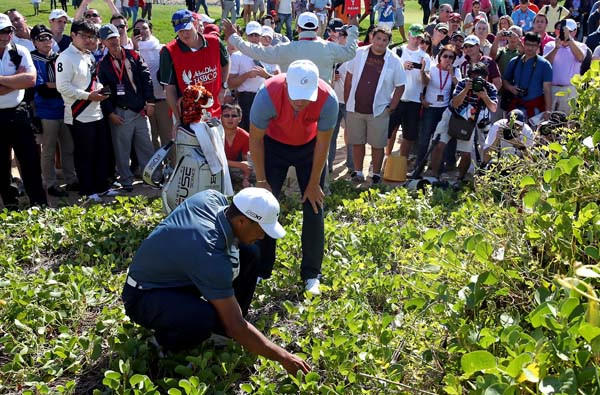 Tiger Woods and Martin Kaymer check on the location of Woods' ball after his drive at the fifth hole Friday in Abu Dhabi.