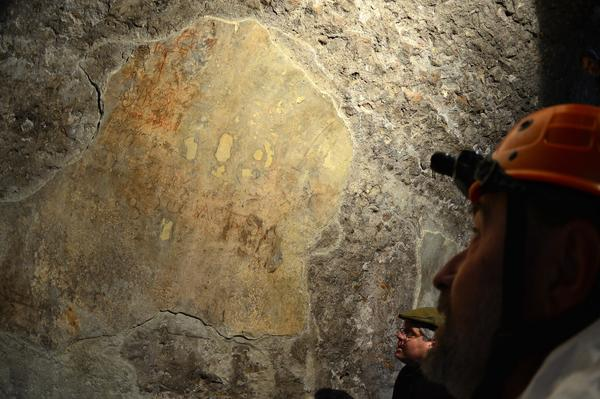 Archaeologist Alessandro Danesi examines brightly colored traces of a fresco found inside a corridor of the Colosseum in Rome.
