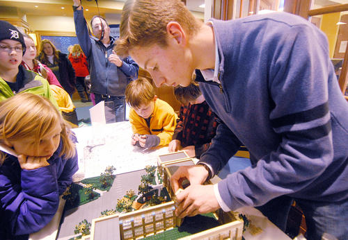 Paul Vermeesch, 16, (far right) of Charlevoix works on a LEGO  model of the Charlevoix Public Library at the library. Vermeesch finished the model Thursday surrounded by a group of enthusiasts of all ages, during the Artist in Action program at the library.  More than 5,000 LEGO pieces from 24 separate sources were used to create the model, which was built with the architect's original plans. Friends of Library covered the cost of materials and Vermeesch donated his months of work and the finished model for permanent display.