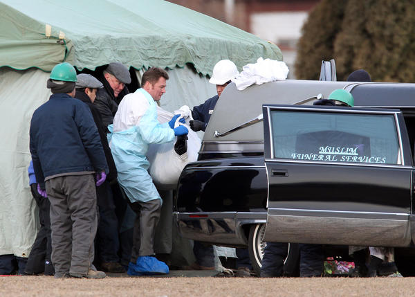 The body of Urooj Khan is moved from his gravesite into a hearse at Rosehill Cemetery in Chicago today.