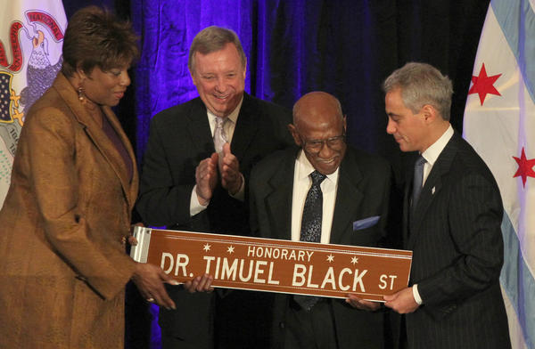 Chicago historian and educator Timuel Black Jr. is presented with an honorary street sign by Ald. Pat Dowell, and Mayor Rahm Emanuel at the 27th annual interfaith breakfast honoring the life of the Rev. Dr. Martin Luther King Jr. U.S. Senator Dick Durbin joins them on the podium.