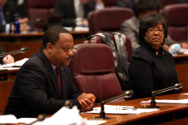Aldermen Roderick Sawyer, 8th, and Michelle Harris, 6th, at a City Council meeting with the empty chair of former Ald. Sandi Jackson between them.