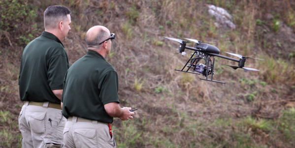 OCSO corporal Jason Robbins and Unmanned Aerial Systems pilot Glenn Miller (right) demonstrate the Dragonflyer X6 drone, during a press conference with Sheriff Jerry Demings, at the sheriff's office gun range in southeast Orange county, Friday, January 18, 2012.