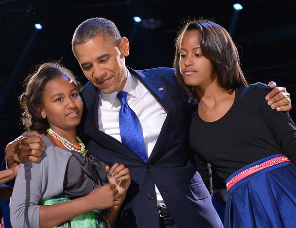 President Barack Obama hugs his daughters Sasham, left, and Malia on election night, Nov. 6, in Chicago.