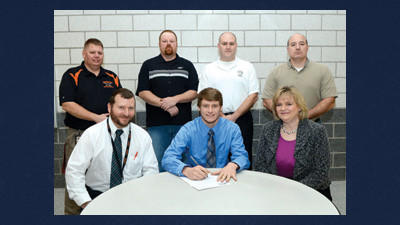 Michael Flyte signs a national letter of intent to play baseball at Mount St. Mary's University while sitting with parents Rick and Becky Flyte. Coaches Steve Costea, Jim Miller, Bob Hay and Lou Dirienzo stand behind.