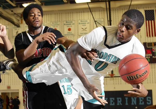 Rob Ostermaier/Daily Press Photo Trevor Lyons of Woodside and Quin Moore of Hampton battle for the rebound during the second half Friday at Woodside.