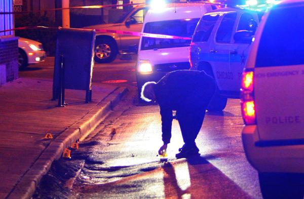 Chicago police investigate the scene at 74th Street and Racine Avenue, where two people were shot.
