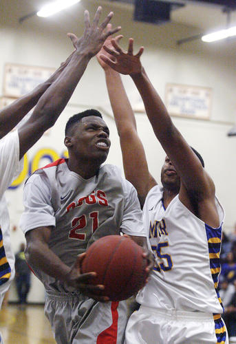 Pasadena's Raymond Jackson moves between Muir defender Taturs Maberry against Muir in a Pacific League boys basketball game at Muir High Schoo on Friday, January 18, 2013.