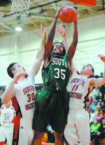 South Hagerstown's Devon King (35) is sandwiched by North Hagerstown's Andrew Yacyk (30) and Max Ober (11) on Friday during the Hubs' 67-63 victory.