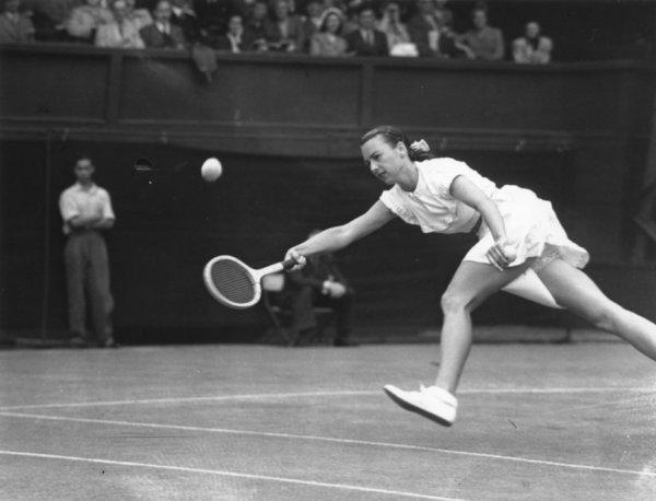 American tennis player Gertrude 'Gussie' Moran stretches for the ball during her match against E M Wilford of Great Britain at Wimbledon on June 22, 1949.